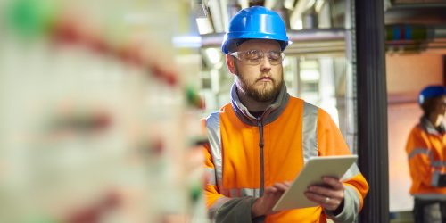 An industrial service engineer conducts a safety check of a control panel in a boiler room. He is wearing hi vis, hard hat, safety glasses and holding a digital tablet as he conducts a safety inspection.